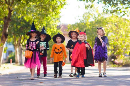 Child in Halloween costume. Mixed race Asian and Caucasian kids trick or treat on suburban street. Little boy and girl with pumpkin lantern and candy bucket. Baby in witch hat. Autumn holiday fun. Imagens