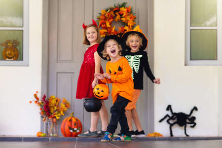 Kids trick or treat on Halloween night. Dressed up children at decorated house door. Boy and girl in witch and vampire costume and hat with candy bucket and pumpkin lantern. Autumn home decoration.