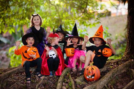 Kind im Halloween-Kostüm. Gemischte asiatische und kaukasische Kinder Süßes oder Saures auf der Vorstadtstraße. Kleiner Junge und Mädchen mit Kürbislaterne und Süßigkeiteneimer. Baby im Hexenhut. Spaß im Herbsturlaub.