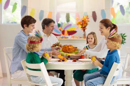 Familia con niños comiendo cena de Acción de Gracias. Pastel de calabaza y pavo asado en la mesa de comedor con decoración otoñal. Comida festiva para padres e hijos. Padre y madre cortando carne. Sombrero de manualidades de papel.