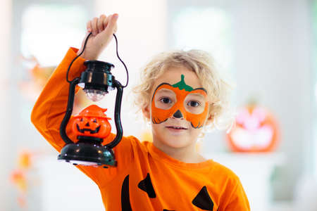 Child in Halloween costume. Kids trick or treat. Little boy with pumpkin face painting and lantern.