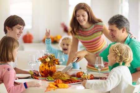 Familie mit Kindern, die Thanksgiving-Dinner essen. Gebratener Truthahn und Kürbiskuchen auf Esstisch mit Herbstdekoration. Eltern und Kinder beim festlichen Essen. Vater und Mutter schneiden Fleisch.
