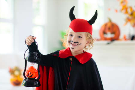 Child in Halloween costume. Kids trick or treat. Little boy dressed as evil vampire with pumpkin lantern.