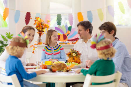 Family with kids eating Thanksgiving dinner. Roasted turkey and pumpkin pie on dining table with autumn decoration. Parents and children festive meal. Father and mother cutting meat. Paper crafts hat. Stok Fotoğraf