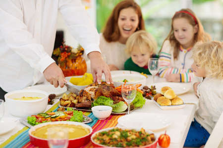Family with kids eating Thanksgiving dinner. Roasted turkey and pumpkin pie on dining table with autumn decoration. Parents and children having festive meal. Father and mother cutting meat. Stok Fotoğraf