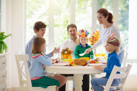 Family with kids eating Thanksgiving dinner. Roasted turkey and pumpkin pie on dining table with autumn decoration. Parents and children festive meal. Father and mother cutting meat. Paper crafts hat. 免版税图像