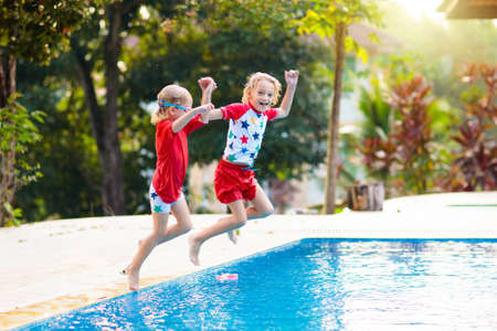 Child playing in swimming pool. Summer vacation with kids. Little boy jumping into water during exotic holiday in tropical island resort. Active outdoor sport for preschooler.