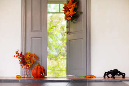 Home entrance decorated for Halloween. Pumpkin lantern and autumn leaves at house front door. Orange and black decoration. Interior ready for trick or treat party or Thanksgiving.