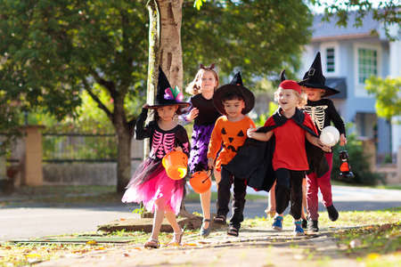 Child in Halloween costume. Mixed race Asian and Caucasian kids trick or treat on suburban street. Little boy and girl with pumpkin lantern and candy bucket. Baby in witch hat. Autumn holiday fun.