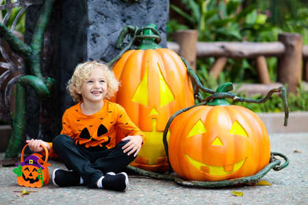 Child in Halloween costume. Kids trick or treat. Little boy dressed with pumpkin lantern. Family celebration. Stok Fotoğraf