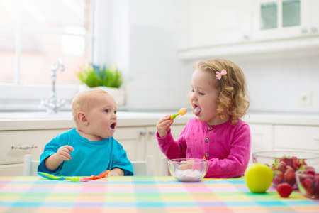 Child having breakfast. Kid drinking milk and eating cereal with fruit. Little boy and girl at white dining table in kitchen at window. Kids eat on sunny morning. Healthy balanced nutrition for kids. Stok Fotoğraf
