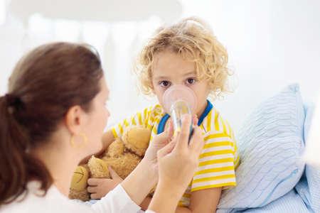 Ragazzino malato con medicina per l'asma. Madre con bambino malato sdraiato a letto. Bambino malato con inalatore a camera per il trattamento della tosse. Stagione influenzale. Genitore in camera da letto o stanza d'ospedale per il giovane paziente.
