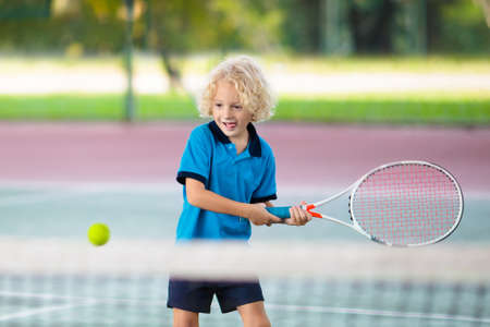 Child playing tennis on indoor court. Little boy with tennis racket and ball in sport club. Active exercise for kids. Summer activities for children. Training for young kid. Child learning to play.