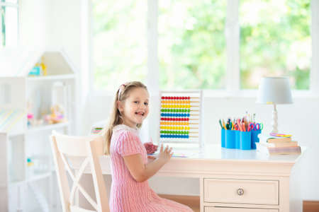 Child drawing rainbow. Kid painting at home. Little girl doing homework after school. Kids desk with abacus in white sunny bedroom. Children study, learn to read and write. Bedroom for young student. Stok Fotoğraf