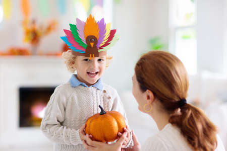 Child and mother celebrate Thanksgiving. Kid holding pumpkin in paper turkey hat. Autumn fun crafts and art. Mom and little boy in decorated living room. Warm knitted wear. Fall season decoration. Stok Fotoğraf