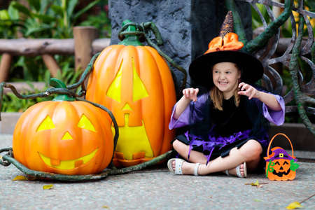 Child in Halloween costume. Kids trick or treat. Little girl dressed as witch with hat holding pumpkin lantern and candy bucket. Family celebration.