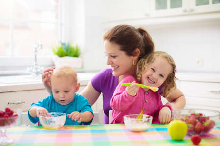 Madre que alimenta al niño con fruta y yogur. Mamá alimenta a niño en la cocina blanca. Niño y niña sentados en la silla alta comiendo un almuerzo saludable de cereales y leche. Nutrición, desayuno saludable para niños pequeños