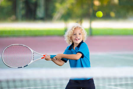 Child playing tennis on indoor court. Little boy with tennis racket and ball in sport club. Active exercise for kids. Summer activities for children. Training for young kid. Child learning to play. Zdjęcie Seryjne