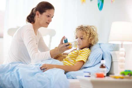 Ragazzino malato con medicina per l'asma. Madre con bambino malato sdraiato a letto. Bambino malato con inalatore a camera per il trattamento della tosse. Stagione influenzale. Genitore in camera da letto o stanza d'ospedale per il giovane paziente. Archivio Fotografico
