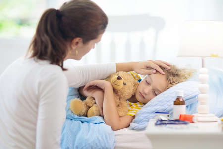 Sick little boy with asthma medicine. Mother with ill child lying in bed. Unwell kid with chamber inhaler for cough treatment. Flu season. Parent in bedroom or hospital room for young patient.