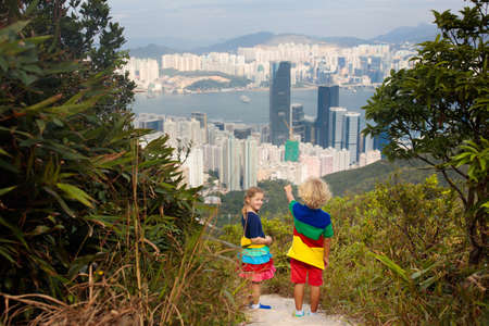 Family with kids hiking in Hong Kong mountains. Beautiful landscape with hills, sea and city skyscrapers in China. Outdoor activity in the nature for parents and children.