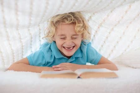 Child reading book in bed under knitted blanket. Kids cozy bedroom hygge style. Little boy doing homework before sleep. Reklamní fotografie