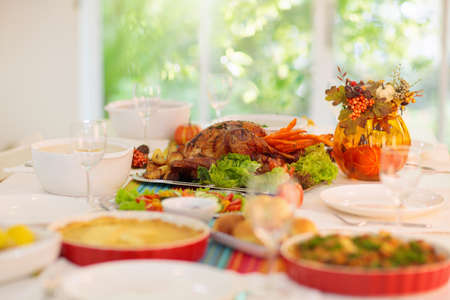 Thanksgiving dinner. Roasted turkey with stuffing and vegetables for family celebration. Autumn holiday table setting. Delicious homemade food and drink at party. Pumpkin and fall leaf decoration.