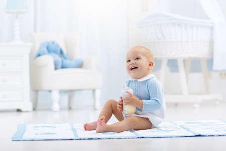 Schattige babyjongen spelen op een blauwe vloermat en consumptiemelk uit een fles in een witte zonnige kinderkamer met schommelstoel en wieg. Slaapkamer interieur met babywieg. Formuledrank voor zuigelingen. Stockfoto