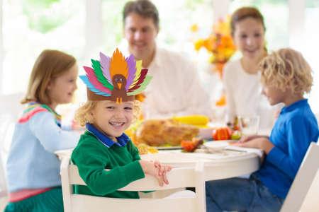 Familie mit Kindern, die Thanksgiving-Dinner essen. Gebratener Truthahn und Kürbiskuchen auf Esstisch mit Herbstdekoration. Eltern und Kinder festliches Essen. Vater und Mutter schneiden Fleisch. Hut aus Papierhandwerk. Standard-Bild