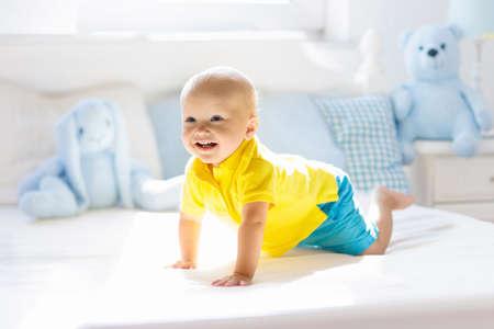 Baby spelen op bed van de ouders. Leuke grappige kleine jongen die leert kruipen in een witte zonnige kinderkamer. Baby en peuter kamer interieur. Beddengoed en speelgoed voor kinderen. Kinderen spelen thuis. Baby slaapkamer.