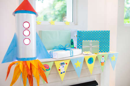 Space theme kids birthday party. Present and gift box on fireplace with banner and balloon. Children event with astronaut, rocket, planets of solar system decoration. Family festive celebration. Stock Photo