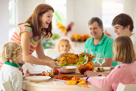 Family with kids eating Thanksgiving dinner. Roasted turkey and pumpkin pie on dining table with autumn decoration. Parents and children having festive meal. Father and mother cutting meat. Stock fotó