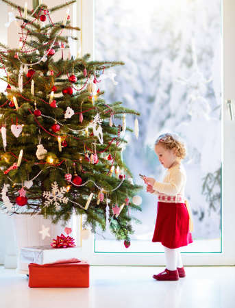 Child decorating Christmas tree at home. Little girl in knitted sweater dress with Xmas ornament. Family with kids celebrate winter holidays. Decorated living room. Opening presents and gifts.