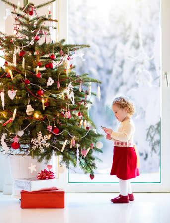 Niño decorando el árbol de Navidad en casa. Niña en vestido de suéter de punto con adorno de Navidad. Familia con niños celebran las vacaciones de invierno. Salón decorado. Apertura de obsequios y obsequios. Foto de archivo
