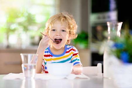Niño desayunando. Niño bebiendo leche y comiendo cereales con frutas. Niño en la mesa de comedor blanca en la cocina en la ventana. Los niños comen en una mañana soleada. Nutrición sana y equilibrada para niños pequeños.