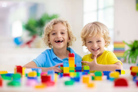 Kids play with colorful blocks. Little boy building tower at home or day care. Educational toy for young child. Construction creative game for baby or toddler kid. Mess in kindergarten playroom. Stock fotó