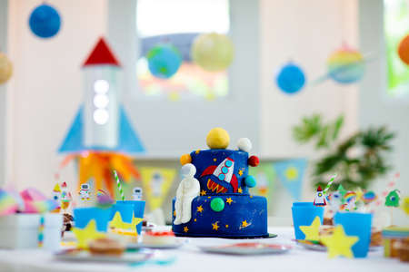 Kids space theme birthday party with cake and cupcakes. Rocket, solar system planet and astronaut decoration for child event. Table setting for little boy celebration with muffin and sweets.