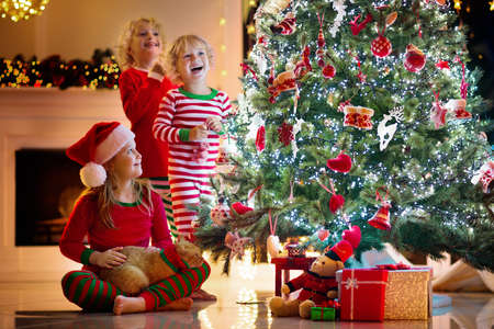 Child decorating Christmas tree at home. Little boy and girl in pajamas with Xmas ornament. Family with kids celebrate winter holidays. Kids decorate living room and fireplace for Christmas.