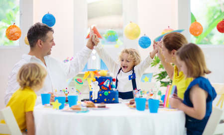 Kids space theme birthday party with cake and cupcakes. Rocket, solar system planet and astronaut decoration for child event. Little boy, friends and parents blowing candles and opening presents.