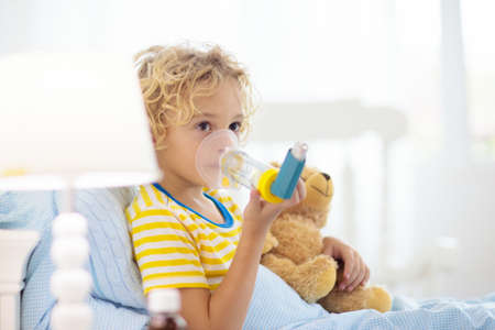 Niño enfermo con medicina para el asma. Niño enfermo acostado en la cama. Niño enfermo con inhalador de cámara para el tratamiento de la tos. Temporada de gripe. Dormitorio o habitación de hospital para paciente joven. Sanidad y medicación.