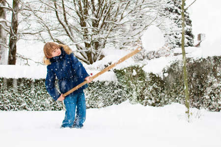 Child shoveling snow. Little boy with spade clearing driveway after winter snowstorm. Kids clear path to house door after Christmas blizzard. Snowfall fun. Children play in cold frosty garden. Stock Photo