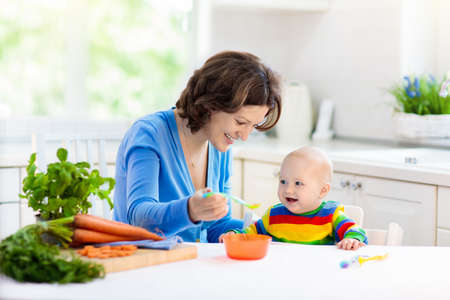 Moeder die kind voedt. Eerste vast voedsel voor jonge kinderen. Verse biologische wortel voor plantaardige lunch. Baby spenen. Mamma en zoontje eten groenten. Gezonde voeding voor kinderen. Ouders voeden kinderen.