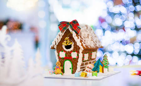 Gingerbread house for Christmas. Baking with kids for winter holidays. Decorated tree and candle lights in living room with fireplace. Pastry and sweets.
