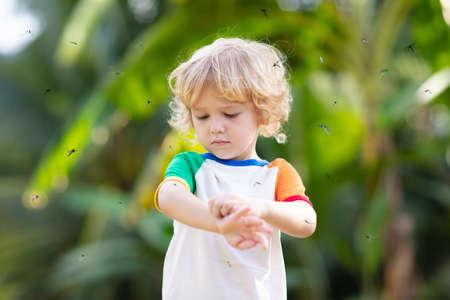 Zanzara sulla pelle dei bambini. Ragazzino attaccato dalle zanzare nella foresta tropicale. Repellente per insetti. Prevenzione della malaria e della febbre dengue. Bambino che graffia il morso pruriginoso nel parco estivo.