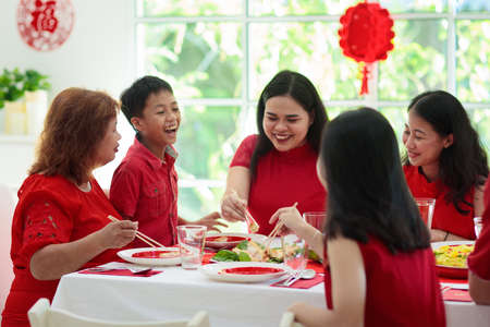 Chinese New Year celebration. Family celebrating winter holiday. Traditional festive dinner in China. Parents, grandparent and kids eating and giving red ang pao envelopes to children. Home decoration