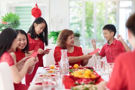 Celebración del año nuevo chino. Familia celebrando las vacaciones de invierno. Cena festiva tradicional en China. Padres, abuelos y niños comiendo y dando sobres rojos ang pao a los niños. Decoración hogareña