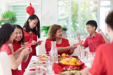 Celebrazione del capodanno cinese. Famiglia che celebra le vacanze invernali. Cena festiva tradizionale in Cina. Genitori, nonni e bambini che mangiano e danno buste rosse ang pao ai bambini. Decorazioni per la casa