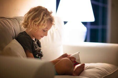 Child reading book. Kids read books. Little boy sitting on white couch in dark living room watching pictures in story book. Kid doing homework for elementary school or kindergarten. Children study.