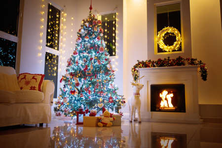 Christmas tree in decorated living room. Family home winter season decoration. Present and gift boxes on Xmas eve. Fireplace with garlands, ornaments and lights. Couch with knitted reindeer cushions.
