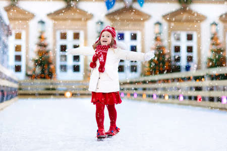 Kids ice skating in winter park rink. Children ice skate on Christmas fair. Little girl with skates on cold snowy day. Snow outdoor fun for child. Winter sports. Xmas vacation activity with kid.